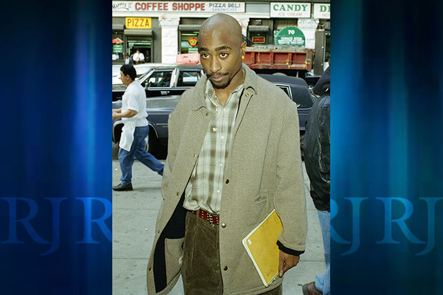 Rapper Tupac Shakur holds a notebook as he waits in line to pass through the metal detectors at New York State Supreme Court in Manhattan, Nov. 14, 1994.  Shakur was charged with sodomy.  (AP Phot ...