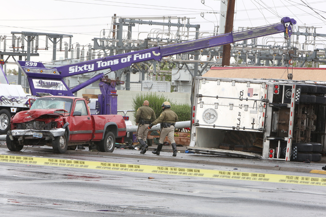 A crane is placed to get a tractor-trailer upright after it overturned in a fatal crash at the intersection of Nellis Boulevard and Washington Avenue, Monday, April 25, 2016. (Bizuayehu Tesfaye/La ...