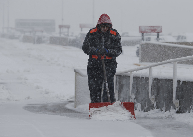 An unidentified maintenance man clears snow from a walkway at Denver International Airport on Saturday, April 16, 2016, in Denver. (David Zalubowski/The Associated Press)