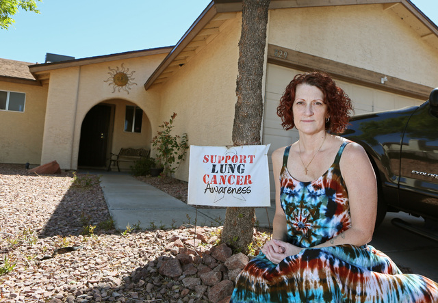Lysa Buonanno sits next to a sign showing her support for lung cancer awareness outside her Henderson home, April 1, 2016. (Ronda Churchill/Las Vegas Review-Journal)