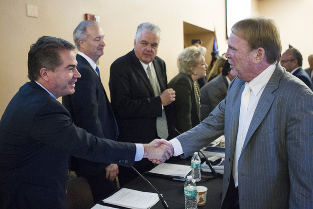 UNLV president Len Jessup, left, shakes hands with Oakland Raiders owner Mark Davis following a meeting to discuss a proposed Las Vegas dome stadium at the Stan Fulton Building at UNLV on Thursday ...