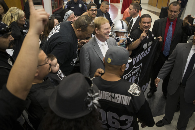 Oakland Raiders owner Mark Davis, center, poses with team fans following press conference on the proposed Las Vegas dome stadium at the Stan Fulton Building at UNLV on Thursday, April 28, 2016, in ...