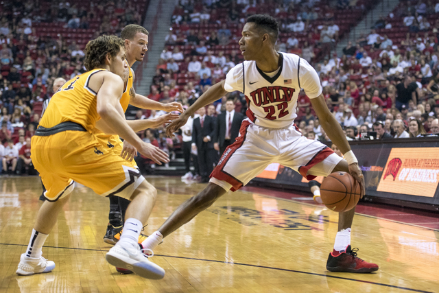 UNLV guard Patrick McCaw (22) is defended by Wyoming guard Jeremy Lieberman (11) and Wyoming guard Josh Adams (14) during the first half at the Thomas & Mack Center in Las Vegas on Saturday, F ...