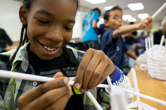 Joshua Lewis makes a basket out of recycled paper in 2013 at Whitney Elementary's after-school program, Village of Hope, which offers a safe environment for at-risk students. Summerlin-based non ...