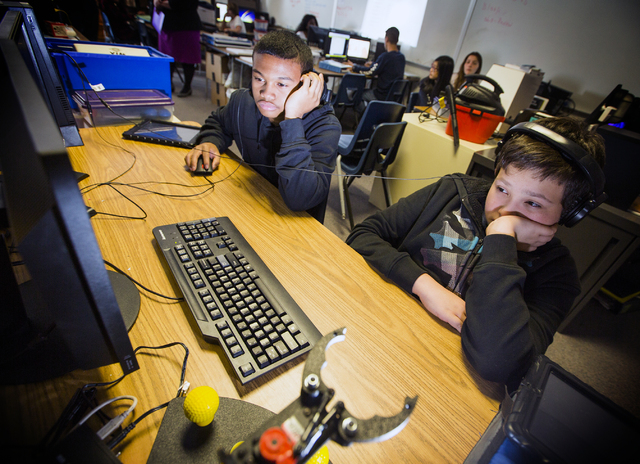 Silvestri Junior High School students Trajon Saap, left, and Trevor Gates views a robotics video during class on Tuesday, March 29, 2016. The school recently received a $14.1 million grant to purc ...