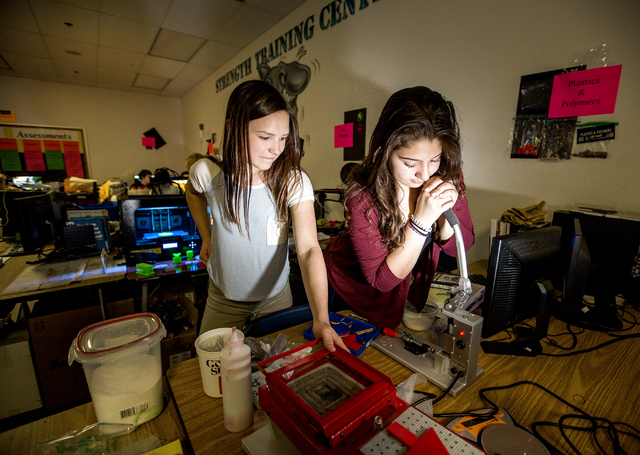 Silvestri Junior High School students Abby Blumberg, left, and Angie Sanchez, press plastic golf tees during class on Tuesday, March 29, 2016. The school recently received a $14.1 million grant to ...
