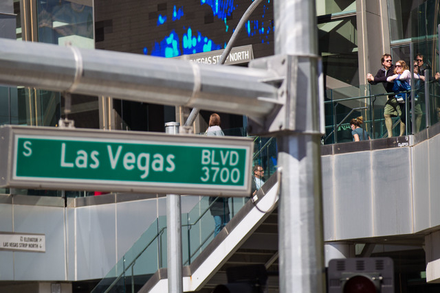 People walk and take in the sights along a pedestrian bridge over Las Vegas Boulevard at Harmon Avenue in Las Vegas on Wednesday, March 4, 2015. (Chase Stevens/Las Vegas Review-Journal)