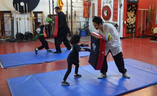 Alicia Young, 5, works with Alex Baginski as her brother Ethan works in the background with instructor Christopher Nason in a children's class at the Lohan School of Shaolin, 3850 Schiff Drive. Gi ...