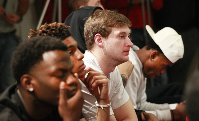 Texas Tech basketball player Matthew Temple, center, and teammates listen as Texas Tech athletic director Kirby Hocutt announces that men's basketball coach Tubby Smith has left the program to coa ...