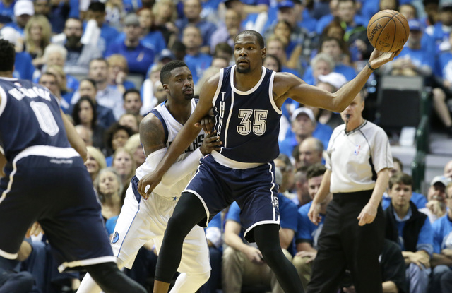 Oklahoma City Thunder forward Kevin Durant (35) keeps the ball from Dallas Mavericks guard Wesley Matthews (23) during the second half in Game 3 of a first-round NBA basketball playoff series Thur ...