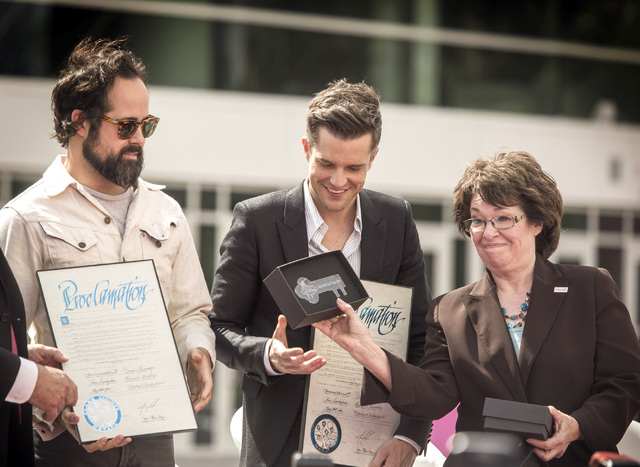 Clark County Commissioner Mary Beth Scow, right, presents the Key to the County to The Killers band members Ronnie Vannucci, left, and Brandon Flowers during a press conference at Toshiba Plaza on ...