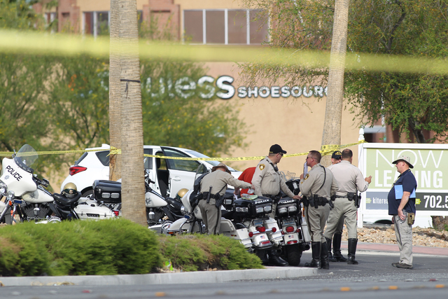 Police gather at an entrance to Walmart near the scene of a fatal accident on Tropical Parkway near Centennial Center Boulevard involving a box truck and two cars in Las Veags on Thursday, April 2 ...