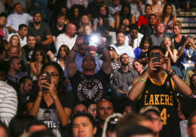 Fans take pictures before the start of a flyweight championship bout between Demetrious Johnson and Henry Cejudo in UFC 197 at the MGM Grand Garden Arena in Las Vegas on Saturday, April 23, 2016.  ...