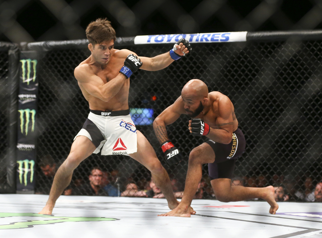 Henry Cejudo, left, dodges a punch from Demetrious Johnson during a flyweight championship bout in UFC 197 at the MGM Grand Garden Arena in Las Vegas on Saturday, April 23, 2016. Johnson won in th ...