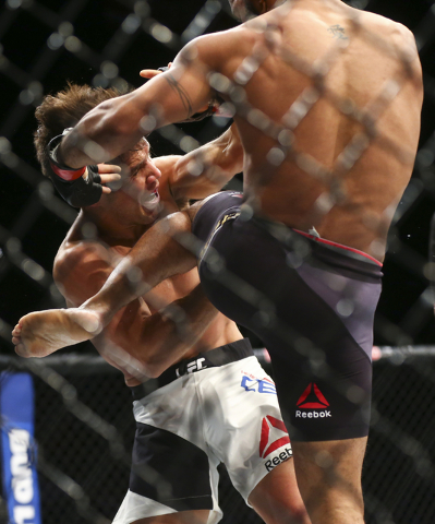 Demetrious Johnson, right, lands a knee against Henry Cejudo during a flyweight championship bout in UFC 197 at the MGM Grand Garden Arena in Las Vegas on Saturday, April 23, 2016. Johnson won in  ...