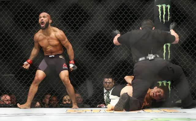 Demetrious Johnson, left, celebrates his technical knockout over Henry Cejudo in the first round of a flyweight championship bout in UFC 197 at the MGM Grand Garden Arena in Las Vegas on Saturday, ...