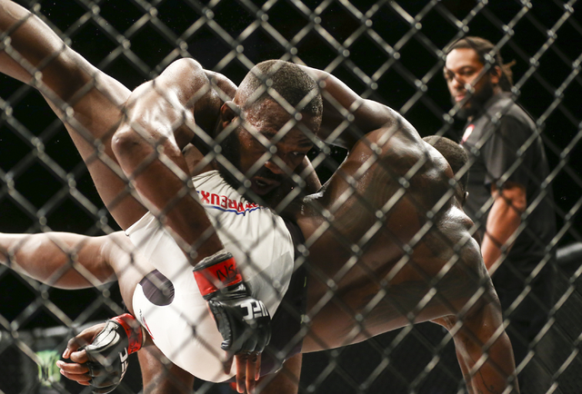 Jon Jones, left, takes Ovince Saint Preux to the mat during an interim light heavyweight championship bout in UFC 197 at the MGM Grand Garden Arena in Las Vegas on Saturday, April 23, 2016. Jones  ...