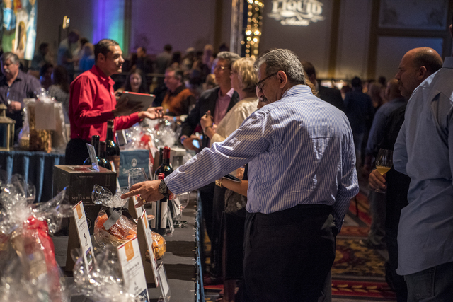 Attendees browse silent auction items during the UNLVino fundraiser at the Paris hotel-casino in Las Vegas on Saturday, April 16, 2016. (Joshua Dahl/Las Vegas Review-Journal)