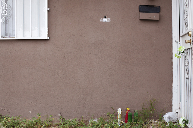 A bullet hole in the wall of the house near candles and flowers is seen Monday, April 25, on the 2400 block of Page Street where a 24-year-old man was found shot to death early Sunday morning in L ...