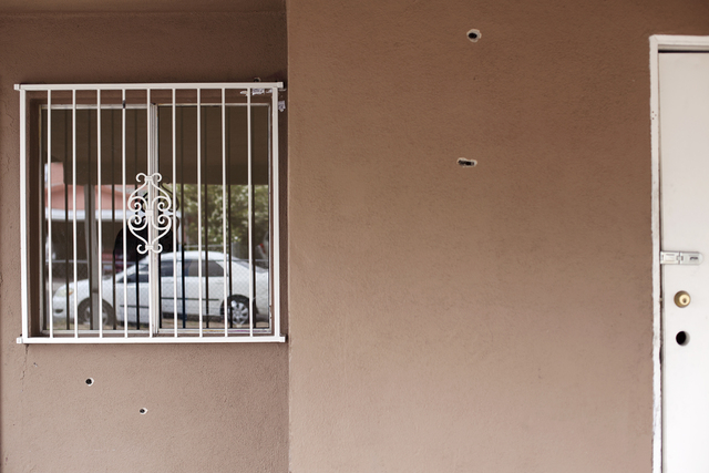 Bullet holes are seen Monday, April 25, on the front walls of the house at the 2400 block of Page Street where a 24-year-old man was found shot to death early Sunday morning in North Las Vegas. (R ...