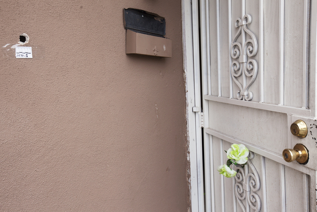 A bullet hole and a fake flower are seen Monday, April 25, in the front of the house at the 2400 block of Page Street where a 24-year-old man was found shot to death early Sunday morning in North  ...