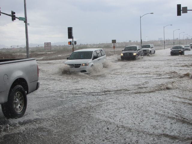 Vehicles slow down to navigate high water at the intersection of Lone Mountain Road and Clayton Street in North Las Vegas on Saturday, April 9, 2016. Greg Haas/Las Vegas Review-Journal Follow @RJg ...