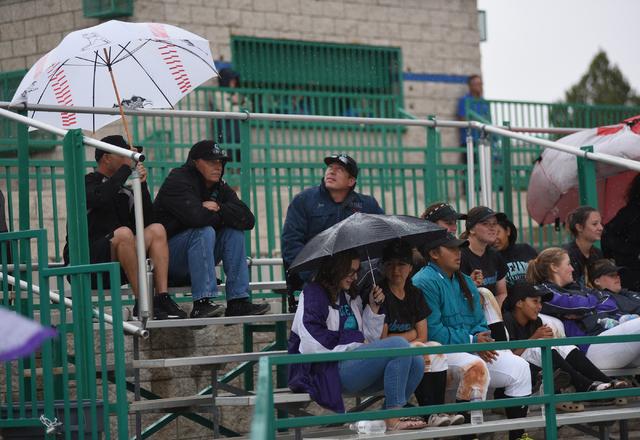 Spectators brave the rain as they watch a baseball game played between Green Valley and Silverado played at Green Valley's Fairless Field in Henderson on Saturday, April 9, 2015. Silverado defeate ...