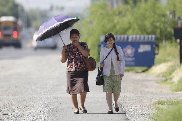 A woman holds her umbrella to protect herself from sun as she walks with her friend along Walnut Street in Las Vegas, Tuesday, April 19, 2016, in Las Vegas. Tuesday will have sunny skies with a hi ...