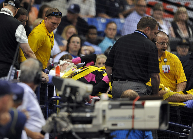 Medical personnel carry a fan from the stands by stretcher after she was hit a foul ball from Tampa Bay Rays designated hitter Steven Souza Jr. during the seventh inning of a baseball game against ...