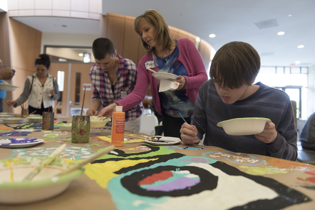 Isaac Antflick, 15, right, Marcy Cherek, center, and Stephanie Helms, second from left, work on a collaborative art project at Yiddish Las Vegas: A Music & Culture Festival at Temple Sinai in  ...