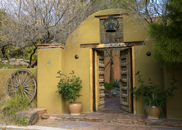 A Santa Fe architect incorporated wood artifacts from Santa Fe, such as corbels, a mission bell and wagon wheels in the yard. The door at the base of the sidewalk was imported from Indonesia. (ELK ...