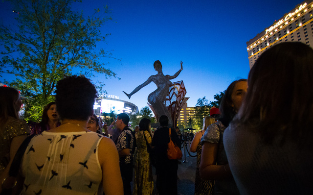 People gather for the lighting ceremony for the 40-foot tall Bliss Dance sculpture at The Park, outside of the T-Mobile Arena and New York New York hotel-casino in Las Vegas on Monday, April 6, 20 ...