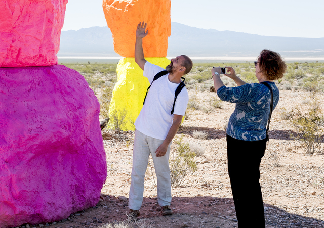 Artist Ugo Rondinone, left, shows off his creation to Carol Cling of the Las Vegas Review-Journal as Art Production Fund and the Nevada Museum of Art celebrate the opening of Seven Magic Mountains ...
