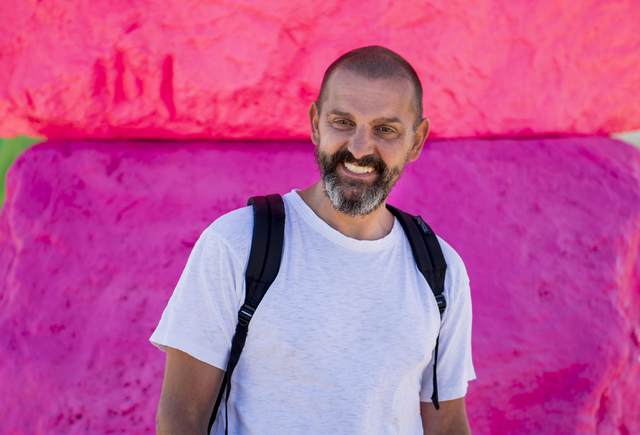 Artist Ugo Rondinone poses near his creation as Art Production Fund and the Nevada Museum of Art celebrate the opening of Seven Magic Mountains -- Rondinone's large-scale, site-specific public art ...