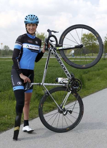 German paralympic cycling athlete Denise Schindler poses with her bicycle in Olching near Munich, Germany, May 2, 2016. Schindler tests the second prototype of a prosthesis made using a new 3D pri ...