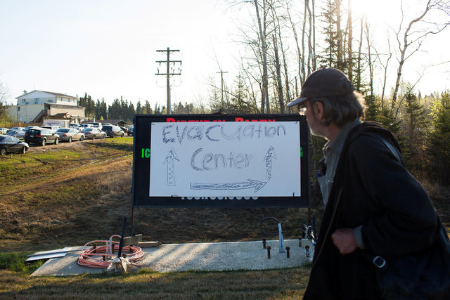 A resident of Fort McMurray walks past a evacuation centre sign put up in Anzac, Alberta, after residents were ordered to be evacuated due to a raging wildfire, May 4, 2016. (Topher Seguin/Reuters)
