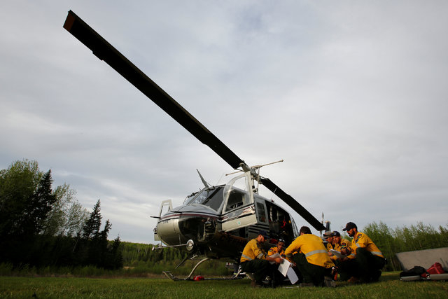 An Alberta wildfire firefighter crew holds a meeting in front of their helicopter while waiting on stanby to respond to new wildfires at a helipad in Lac la Biche, Alberta, Canada, May 7, 2016. (C ...