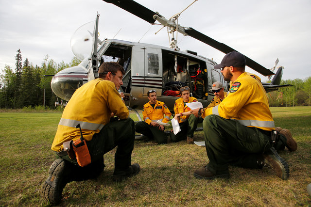 An Alberta wildfire firefighter crew holds a meeting in front of their helicopter while waiting on stanby to respond to new wildfires at a helipad in Lac la Biche, Alberta, Canada, May 7, 2016.(Ch ...