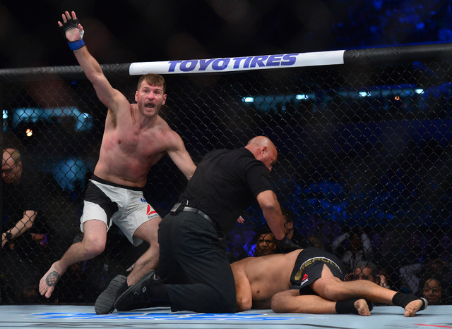 May 14, 2016; Curitiba, Brazil; Stipe Miocic (blue) reacts after defeating Fabricio Werdum (red) during UFC 198 Fight Night at Arena Atletico Paranaense. (Jason Silva/USA Today Sports/Reuters)