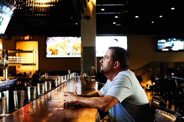 Ben Carson, a carpenter, sits by himself at the bar inside the Williston Brewing Company in Williston, North Dakota, U.S. May 15, 2016.  Revenue at the restaurant is down sixty percent from its pe ...