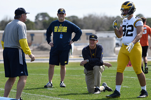 In this Feb. 29, 2016, file photo, Michigan's head coach Jim Harbaugh, center right, watches defensive coordinator Don Brown, left, work with Cheyenn Robertson during team practice in Bradenton, F ...
