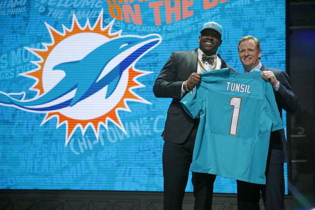 Mississippi's Laremy Tunsil poses for photos with NFL commissioner Roger Goodell after being selected by the Miami Dolphins as the 13th pick in the first round of the 2016 NFL football draft, Thur ...