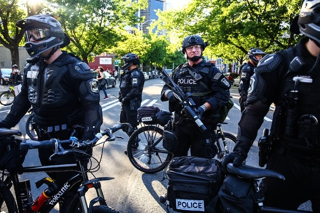 Seattle police officers stand by during an anti-capitalism protest Sunday, May 1, 2016, in Seattle. (Genna Martin/seattlepi.com via Associated Press)