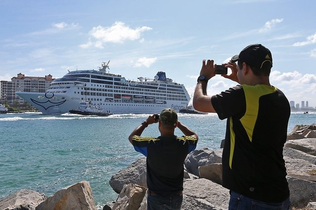 People take photos as Adonia leaves port in Miami, Sunday, May 1, 2016, en route to Cuba. After a half-century of waiting, passengers finally set sail on Sunday from Miami on an historic cruise to ...