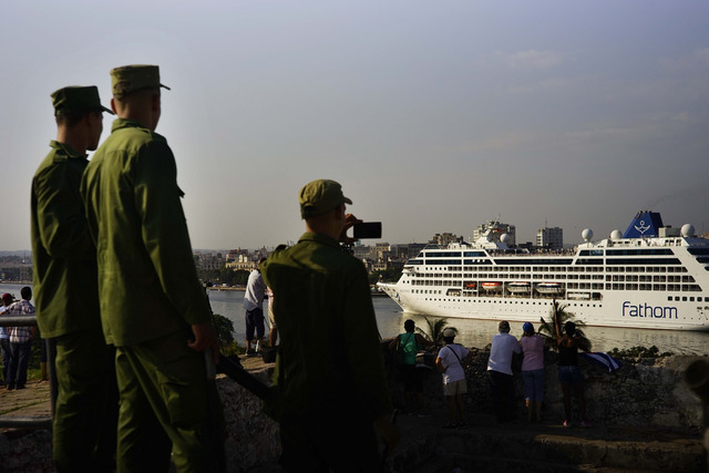 Cuban soldiers watch the Carnival Adonia cruise ship arrive from Miami, in Havana, Cuba, Monday, May 2, 2016. The Adonia's arrival is the first step toward a future in which thousands of ships a y ...