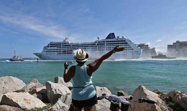 A woman from Cuba waves Adonia leaves port in Miami, Sunday, May 1, 2016, en route to Cuba. After a half-century of waiting, passengers finally set sail on Sunday from Miami on an historic cruise  ...