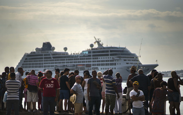 People watch Carnival's Adonia cruise ship arrive from Miami, in Havana, Cuba, Monday, May 2, 2016. The Adonia's arrival is the first step toward a future in which thousands of ships a year could  ...