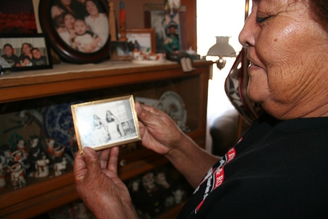 This November 2014 image provided by the American Indian Alaska Native Tourism Association shows Mary Lowden holding a photo of her mother and her aunt, both pottery makers, during a visit to her  ...