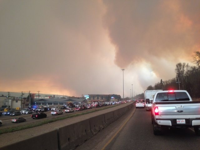 Smoke from a wildfire rises in the air as cars line up on a road in Fort McMurray, Alberta, Tuesday, May 3, 2016. At least half of a northern Alberta city was ordered evacuated Tuesday as a wildfi ...