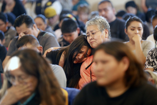 Community members comfort one another during a vigil for Ashlynne Mike at the San Juan Chapter House in Lower Fruitland, N.M., Tuesday, May 3, 2016. The FBI said Ashlynne was abducted after school ...
